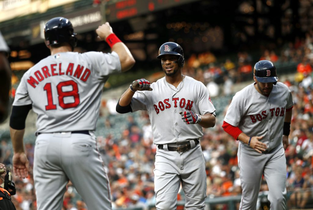 Xander Bogaerts, center, celebrates with Mitch Moreland, left, and J.D. Martinez after hitting a three-run homer in the first inning Friday night against the Baltimore Orioles. Brock Holt and Andrew Benintendi also homered for the Red Sox in a 19-12 win.