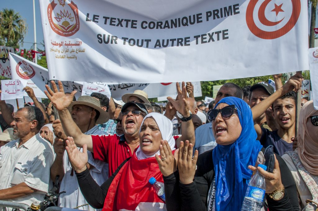 "People demonstrate with a banner reading ""Quran text before any other text"" outside the Tunisian capital of Tunis on Saturday."
