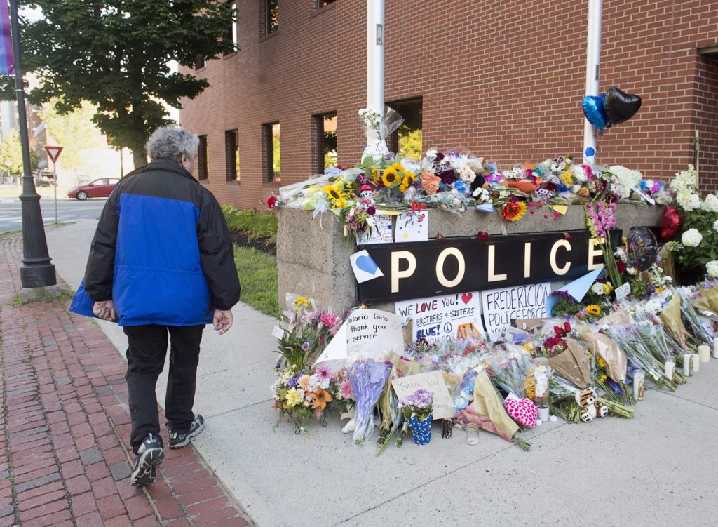 A resident views a makeshift tribute outside the police station in Fredericton on Saturday. Two officers were among four people killed in a shooting in a residential area on the city's north side.