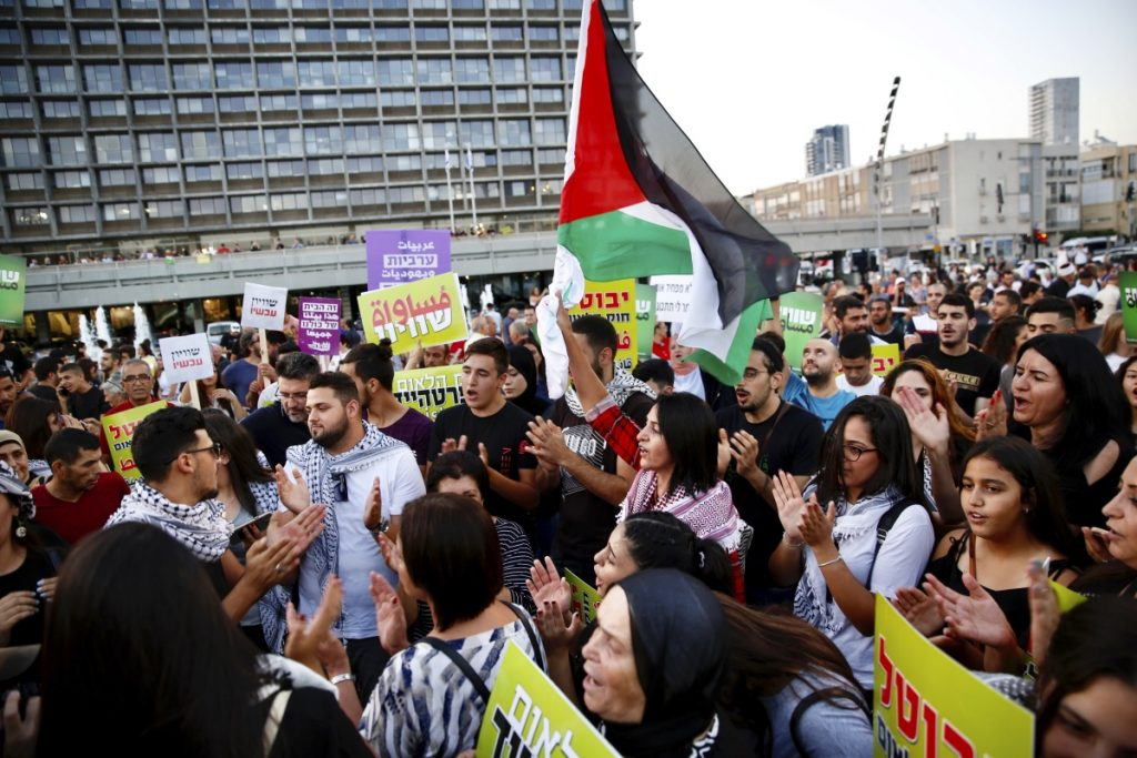 "Israeli Arabs hold a Palestinian flag during a protest against the Jewish nation bill in Tel Aviv on Saturday. The recently passed law enshrines Israel's Jewish character and downgrades the standing of Arabic from an official to a ""special"" language."