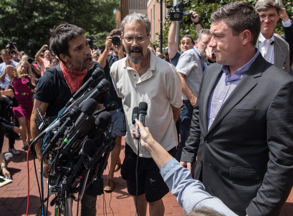 Protesters shout at Jason Kessler, right, during a news conference outside City Hall in Charlottesville, Va., on Aug. 13, a day after an alt-right rally turned into mayhem.