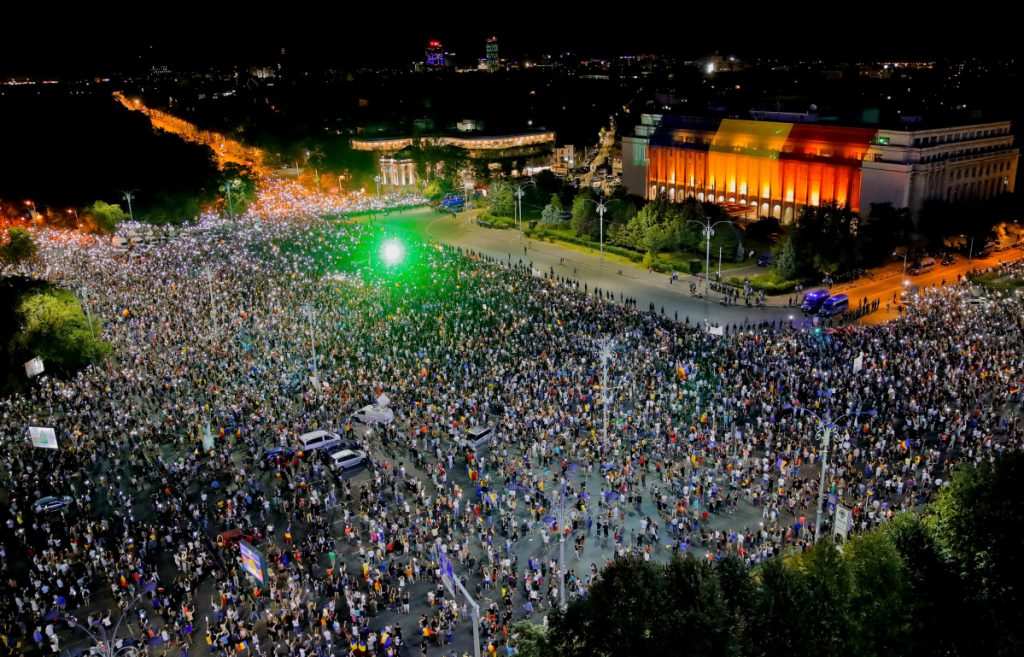 People shine lasers and the lights of their mobile phones during a protest outside the government headquarters in Bucharest, Romania, on Saturday. Romanians gathered for a second day of protest, a day after an anti-government demonstration turned violent.