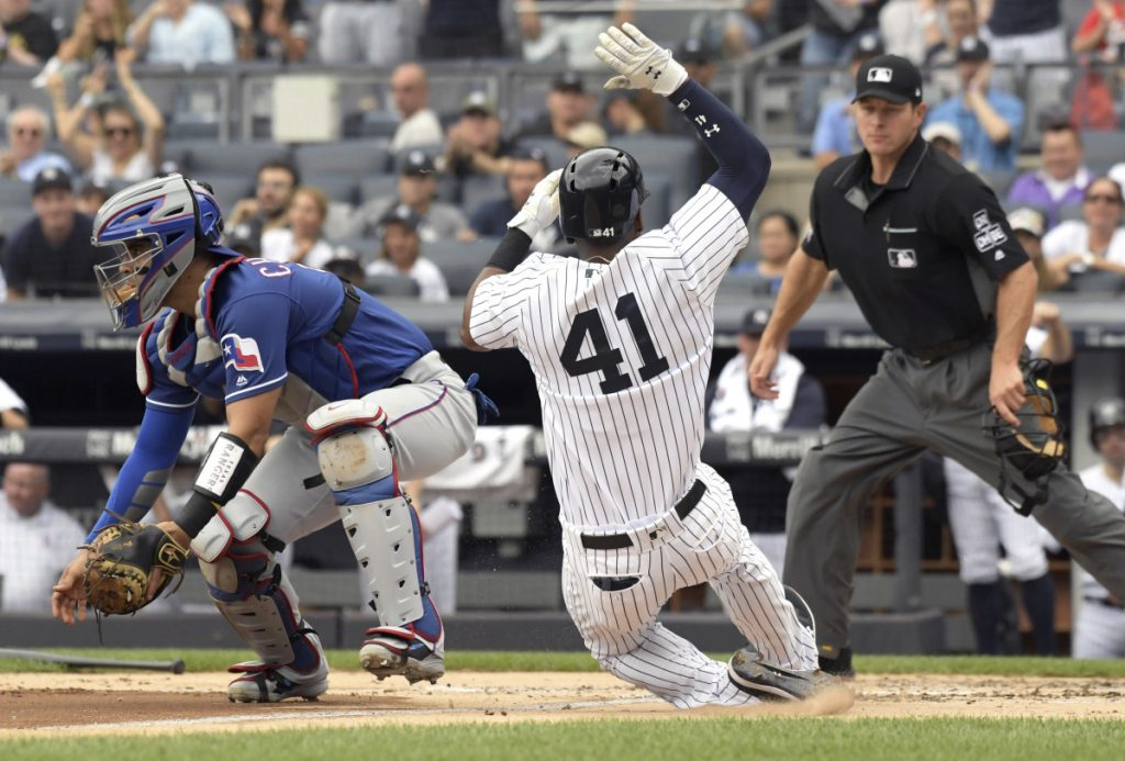Miguel Andujar of the New York Yankees scores on a double by Greg Bird as Texas catcher Robinson Chirinos waits for the ball Saturday. The Yankees won, 5-3.