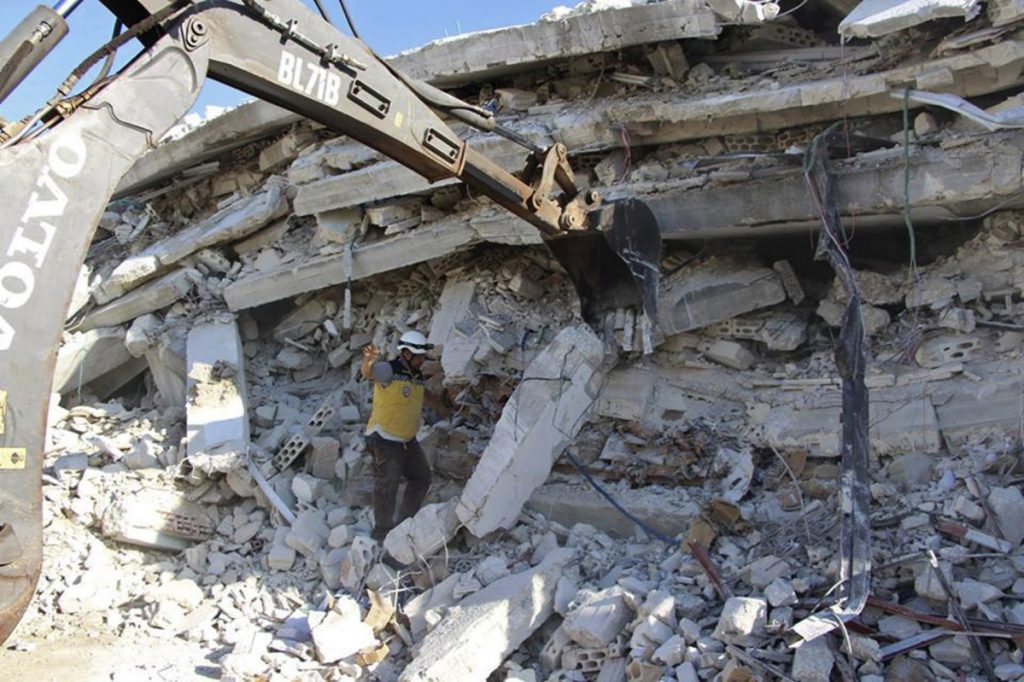 Syrian White Helmet civil defense workers respond to the scene of an explosion that brought down a five-story building in the village of Sarmada, near the Turkish border, in northern Syria on Sunday.