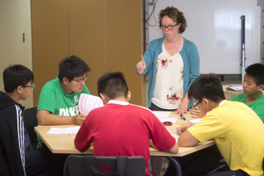 Kathryn Will-Dubyak, an assistant professor in literacy education, works with a group of students from HKMA David Li Kwok Po College in Hong Kong during an English-language learners class at the Kalikow Education Center at the University of Maine at Farmington.