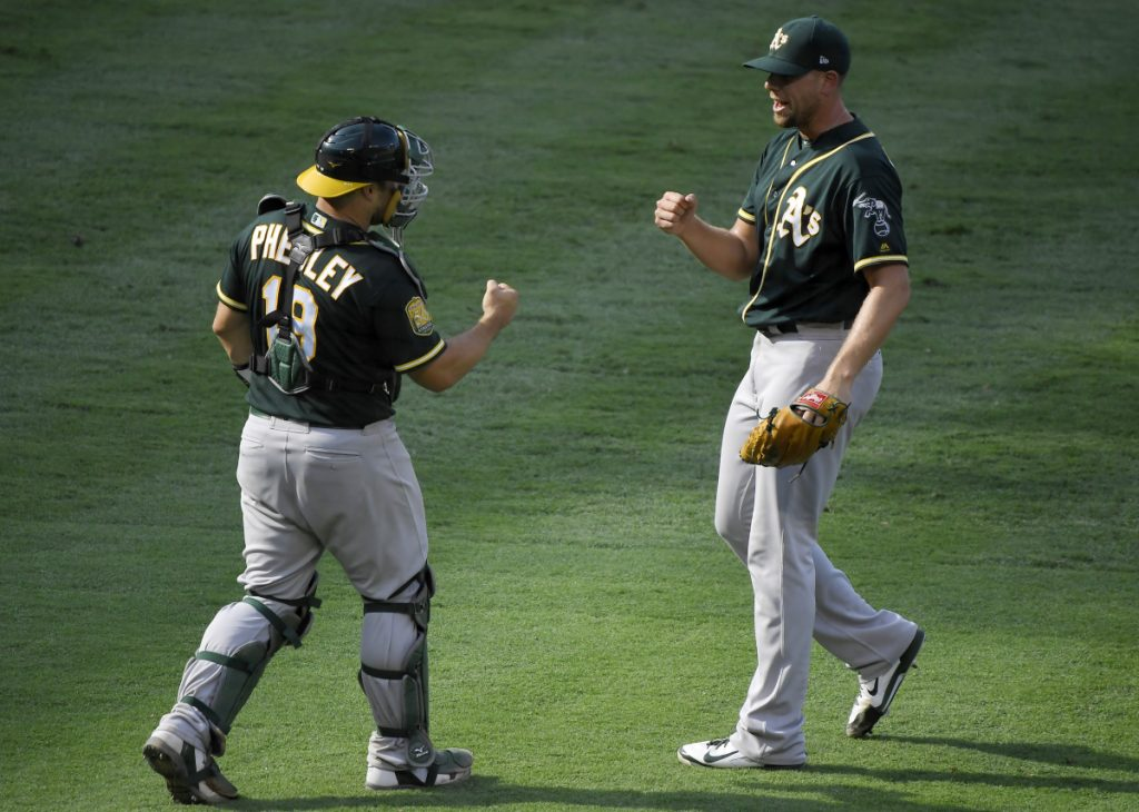 Oakland Athletics catcher Josh Phegley, left, and relief pitcher Blake Treinen congratulate each other after another victory. The A's have risen to offer a challenge to Houston and Seattle in the AL West.