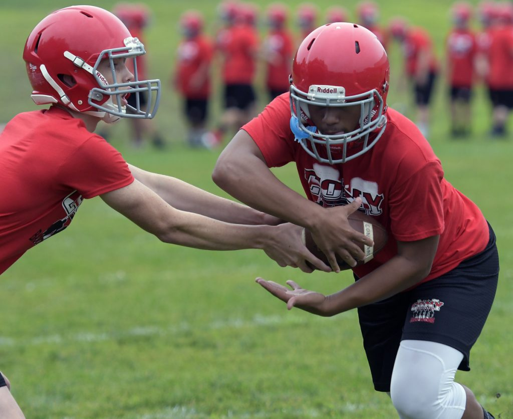 Cony High School football players work on a handoff during practice Monday morning in Augusta. Monday marked the first day fall sports teams could start practicing.