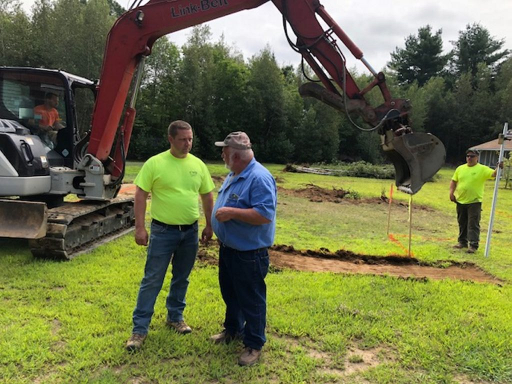Mickey Wing, right, of Central Maine Disposal and Excavation, confers with Joel Violette, of Fairfield Drafting & Construction, about plans for a new home for Sheryl Cole.