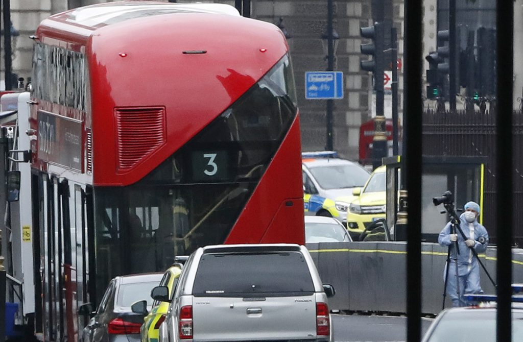 A forensics officers works near the scene near a car that crashed into security barriers outside the Houses of Parliament to the right of a bus in London. London police say the incident is being treated as a terrorist attack.