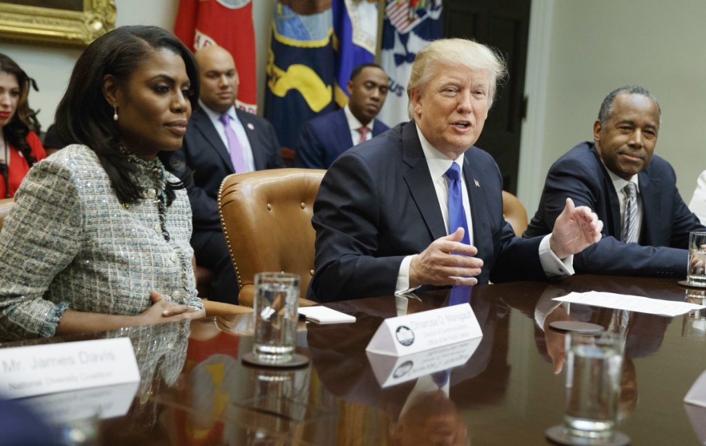 "President Trump is flanked by White House staffer Omarosa Manigault Newman, left, and  then-Housing and Urban Development Secretary-designate Ben Carson as he speaks during a meeting on African American History Month in the Roosevelt Room of the White House in Washington. Manigault Newman, who was fired in December, released a new book ""Unhinged,"" about her time in the White House."