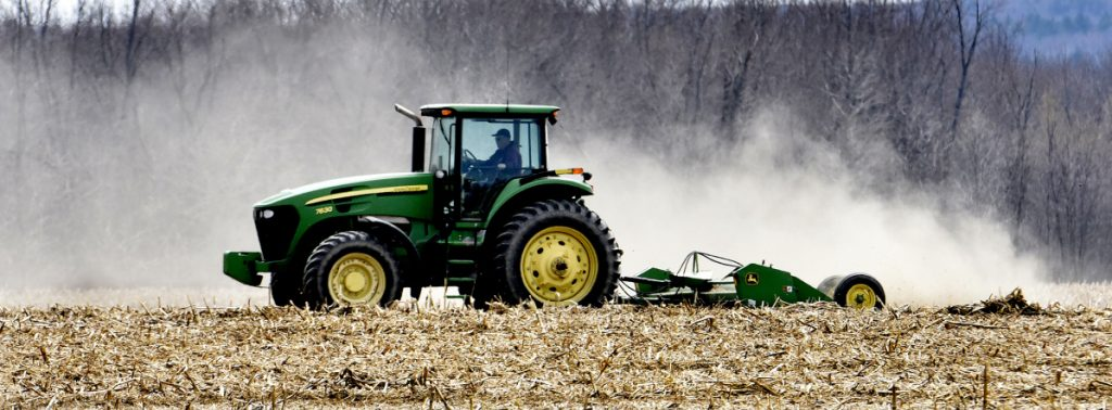 Dairy farmer Bussie York chops corn stalks at the Sandy River farm he owns in Farmington. He wants to lease 700 acres to a company that plans to install more than 300,000 solar panels. Developer NextEra says it would be the largest solar project in New England.