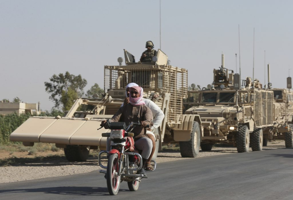 People ride past U.S. armored vehicles in Raqqa, Syria in July 2017. Figures obtained by the U.S. government and United Nations show The Islamic State may still have more than 30,000 militants in Syria and Iraq despite eradication attempts.