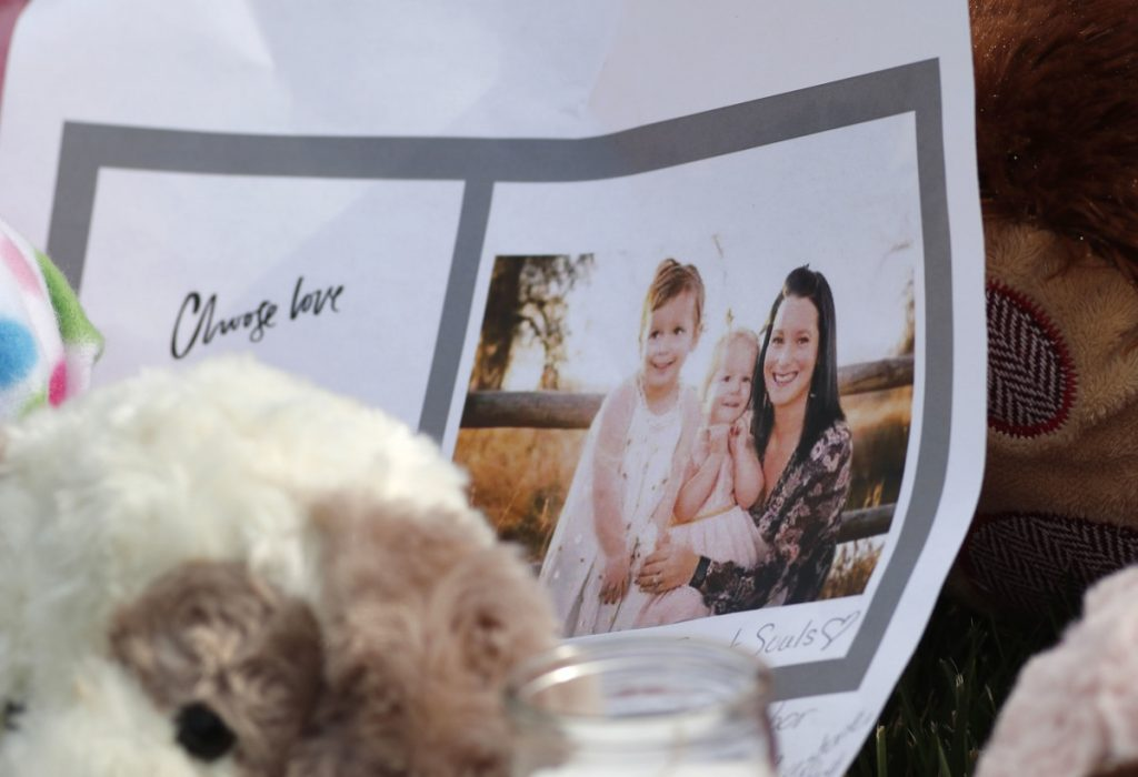 A photograph sits amid tributes as they grow outside the home where a pregnant woman, Shanann Watts, and her two daughters, Bella and Celeste, lived Thursday in Frederick, Colo.