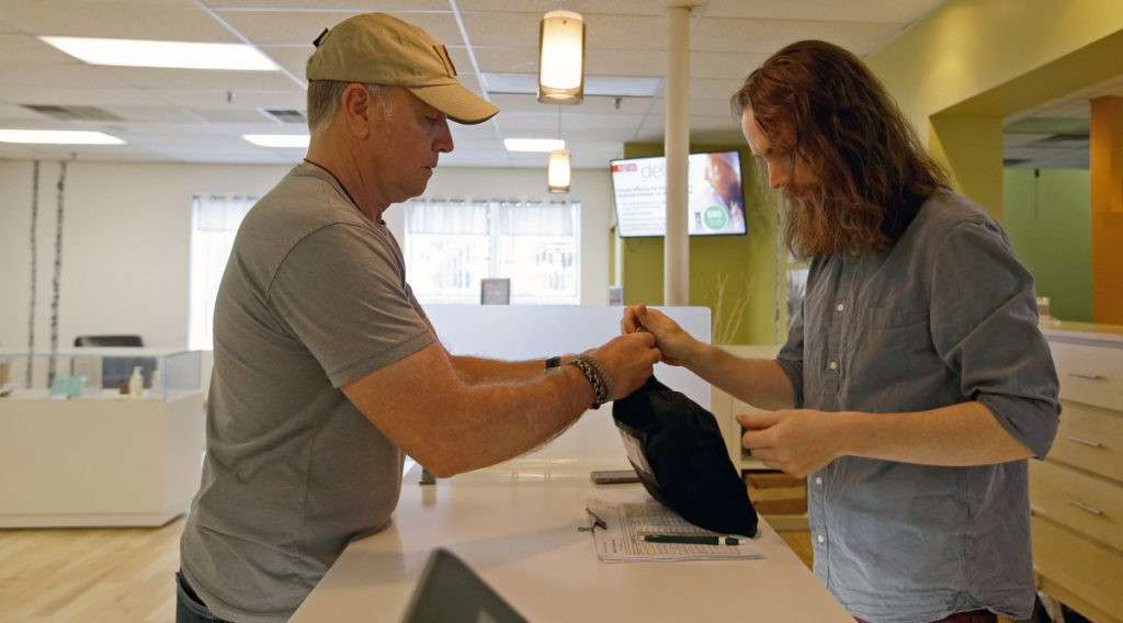 Scott Durst, left, retired from the Maine Drug Enforcement Agency, receives a deposit bag of cash from Kyle Dunn, manager of Wellness Connection, a dispensary in Portland.