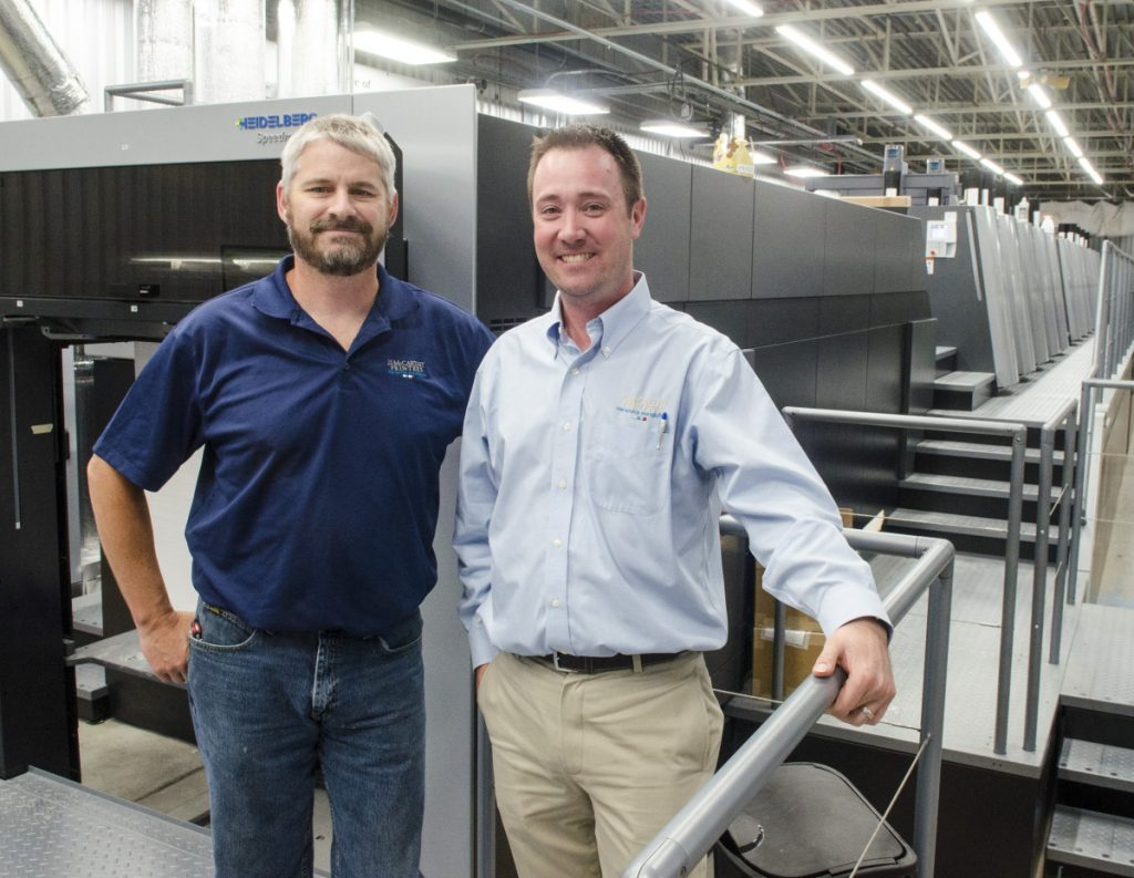 Press room manager Randy Robbins, left, and President and CEO Jon Tardiff pose with the new Heidelberg press in Augusta.