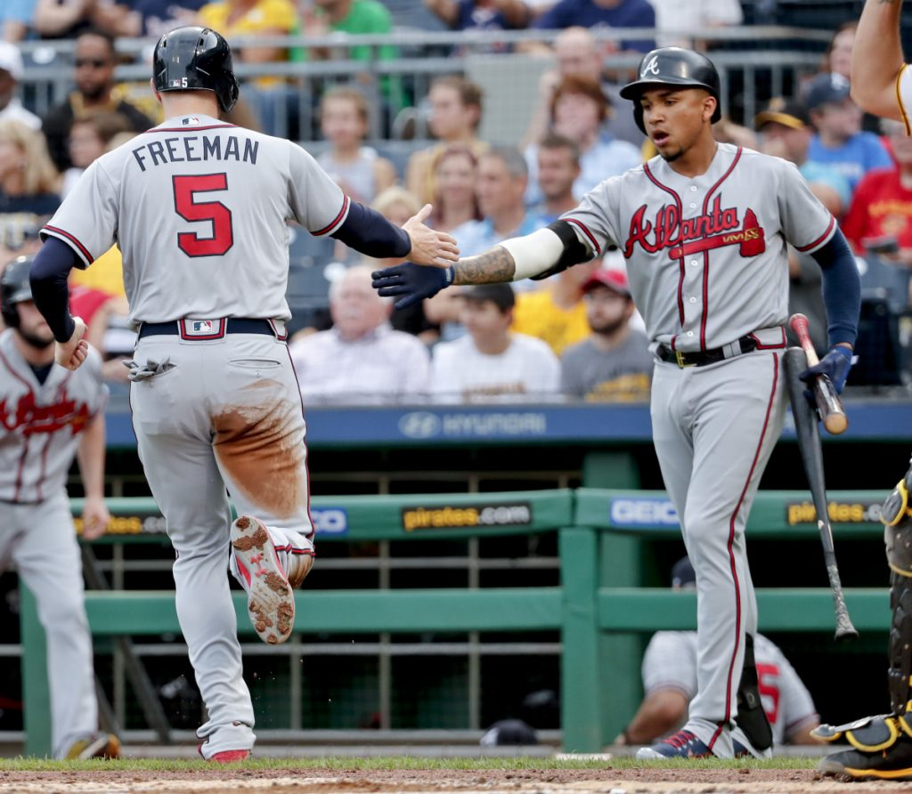 Freddie Freeman of the Atlanta Braves is greeted by teammate Johan Camargo after scoring from second on a single by Nick Markakis in the first inning of a 1-0 victory Monday night against the Pittsburgh Pirates.
