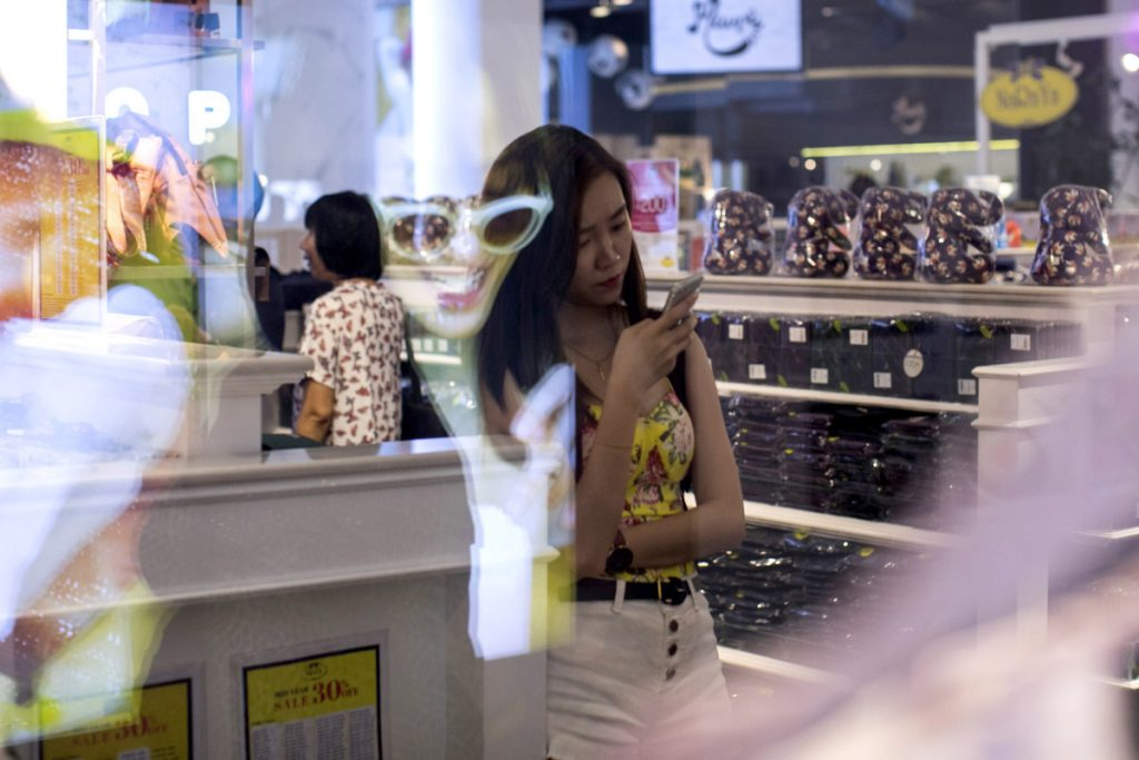 """A shopper looks at a smartphone at a mall in Bangkok, Thailand, in June. By 2020, more than half of the world's population will be """"middle class,"""" one researcher says."""