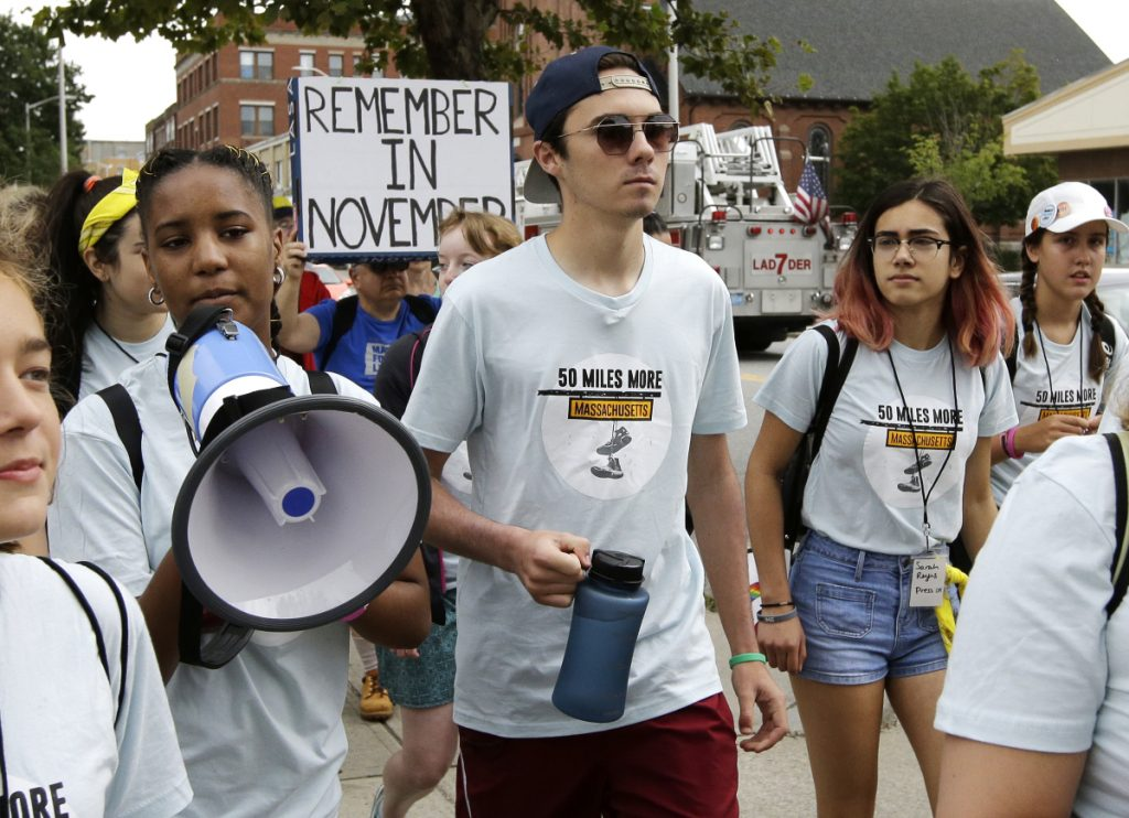 David Hogg, center, a survivor of the school shooting at Marjory Stoneman Douglas High School in Parkland, Fla., walks in a planned 50-mile march Thursday in Worcester, Mass. The march is being held to call for gun law reforms.