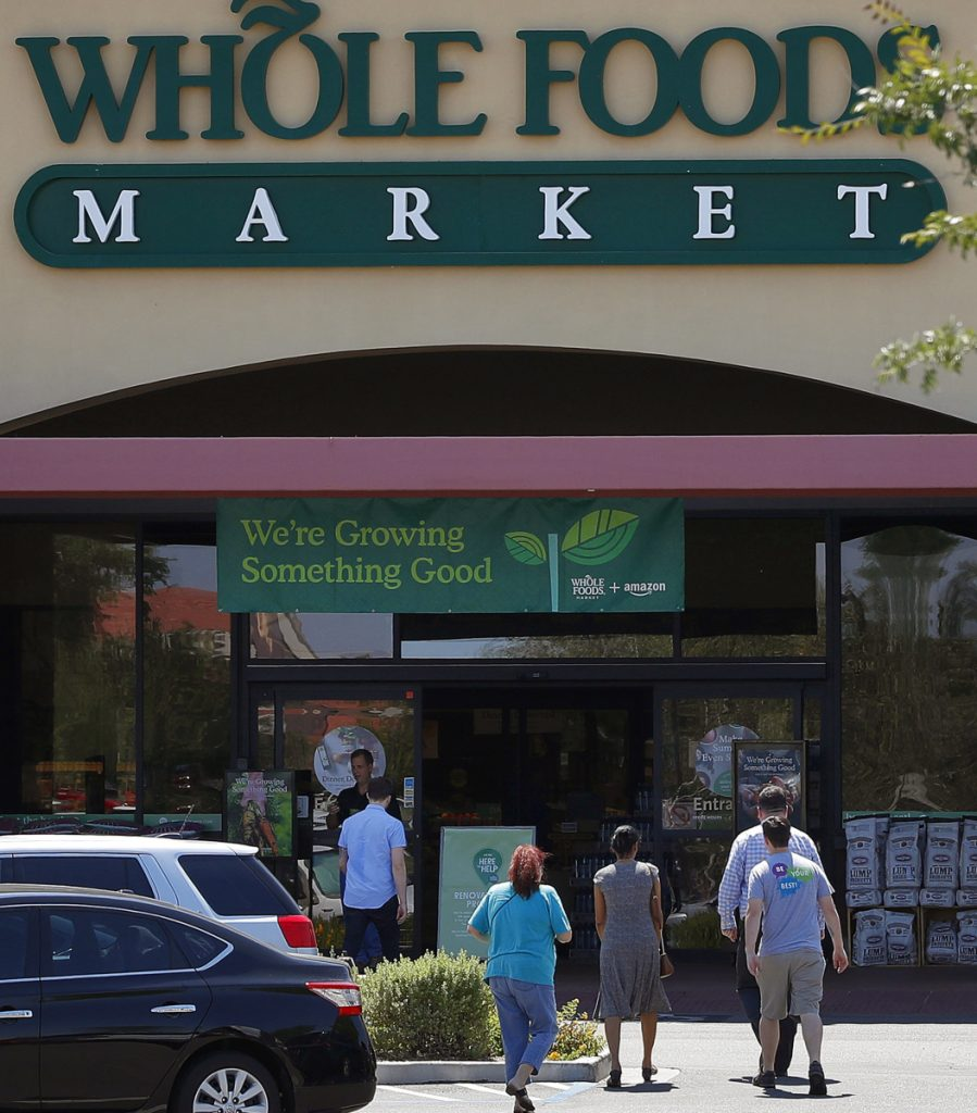 Shoppers come and go from a Whole Foods Market in Chandler, Ariz., in 2017. Amazon moved swiftly to say it planned to cut prices on bananas, eggs, salmon, beef and more.