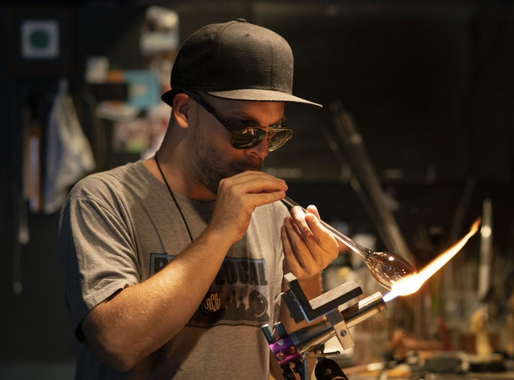 1886f77386d ... worker Brian Owoc blows into a blowing tube while creating a glass  doughnut pipe in his Portland studio on Monday