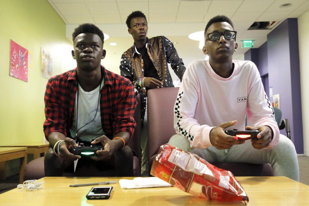 Paul Kana, left, plays EA Sports' FIFA video game against Abdirahim Mohamed in Portland, while Philip Kana assumes the role of referee. The average teen spends nine hours a day looking at a screen, a 2015 Common Sense Media survey found. Staff photo by Ben McCanna