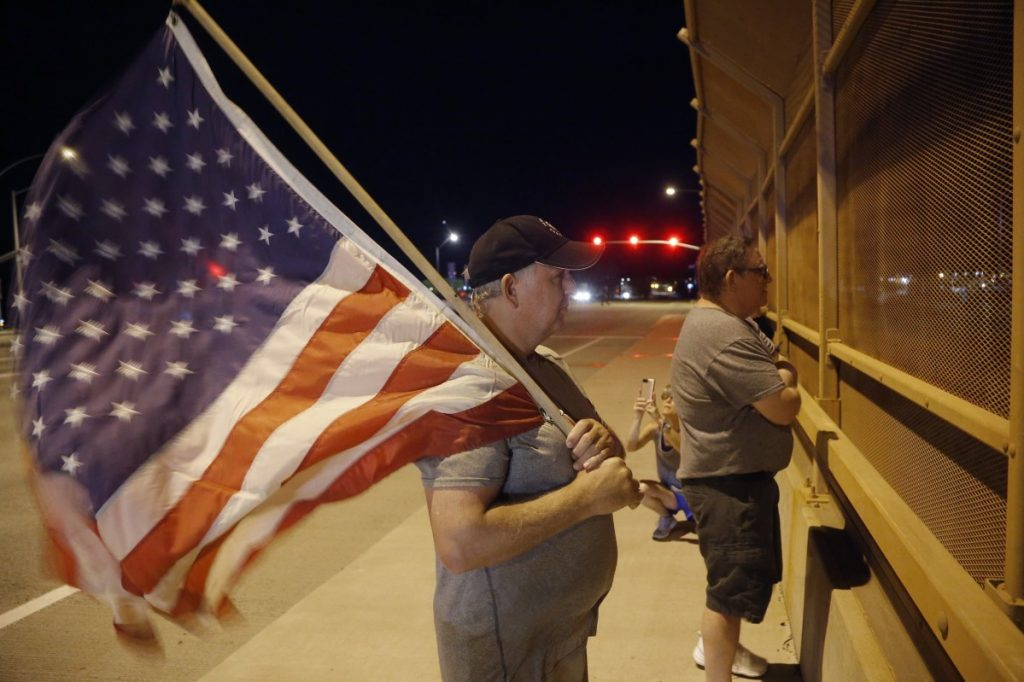 Joe Gruber, of Anthem, Ariz., holds an American flag at an overpass along Interstate 17 as he and dozens of others wait for the procession with the hearse carrying the late Arizona Sen. John McCain on Saturday night.