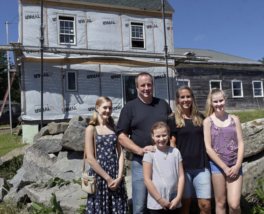 John Pagurko stands with his wife, Melanie, and their daughters, from left, Calista, Christina and Shae-Lynn on Thursday outside the home they are rebuilding in Whitefield following a destructive fire last year. Church and community volunteers are helping with both the building and the fundraising.