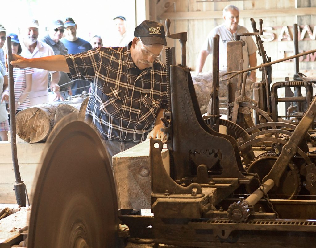 Bob Brann, left, and Jim Hawkes cut a log Sunday at the sawmill recently reassembled at the Windsor Fairgrounds.
