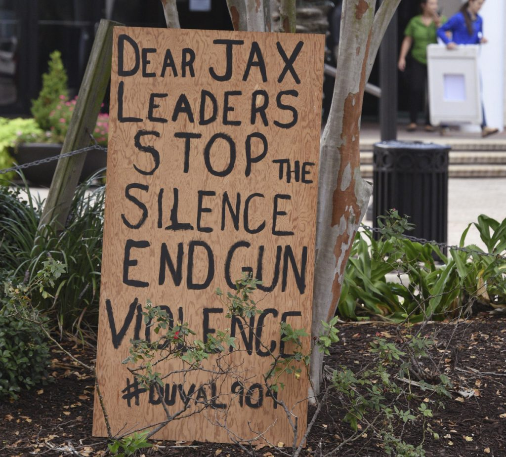 A sign is placed outside the site of a mass shooting Sunday in Jacksonville, Fla.