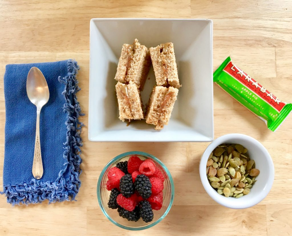 A simple vegan lunchbox meal includes sunbutter and jam sandwich squares, fresh mixed berries, roasted pumpkin seeds with golden raisins, and an apple pie Larabar.