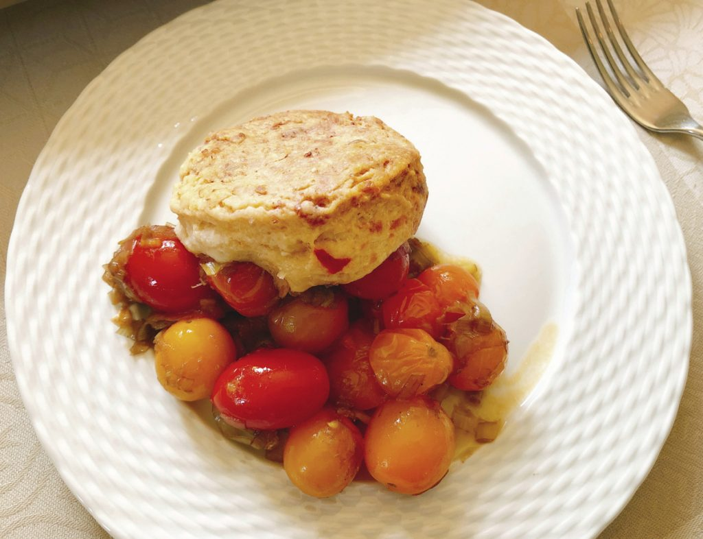 The writer wanted the cobbler to be simple and showcase the fresh vine-ripened local tomatoes, so she stuck to essentially two ingredients: leeks and tomatoes.