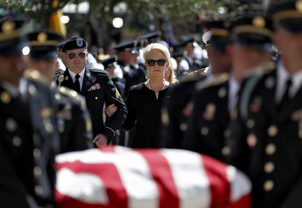 Cindy McCain escorted by her son, Jimmy McCain, left, follow military personnel carrying the casket of Sen. John McCain, R-Ariz., into the Capitol rotunda for a memorial service on Wednesday at the Capitol in Phoenix.