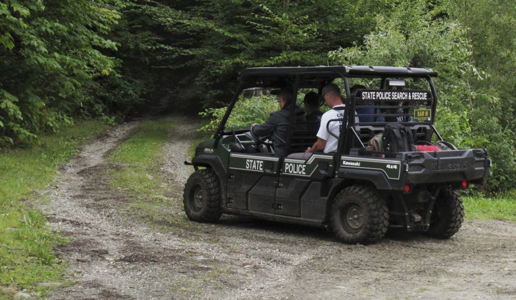 Recovery crews head into the woods of Vermont's Sterling Mountain, Thursday, in Morristown, Vt., to help transport out the bodies of three people killed in a glider crash.