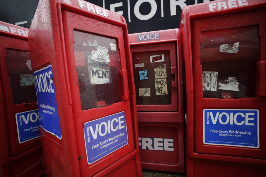 In this Nov. 27, 2013, photo, plastic newspaper boxes for The Village Voice stand along a Manhattan sidewalk in New York. Village Voice publisher Peter Barbey announced Friday that the venerable alternative weekly will cease publication. The announcement comes three years after Barbey bought the paper and one year after it ceased publishing in print.