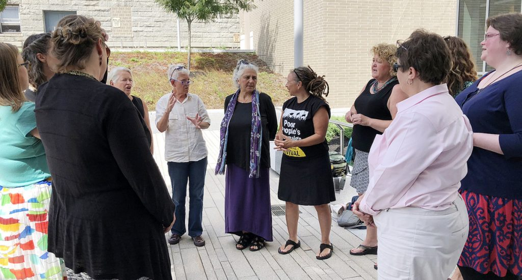 Defendants charged May 14, with criminal trespass at the Blaine House confer with each other and with one of their attorneys Tuesday after a hearing at the Capital Judicial Center.