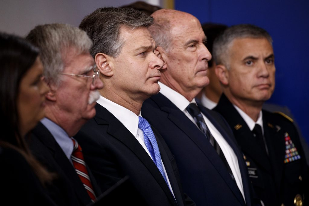 FBI Director Christopher Wray listens during the daily press briefing at the White House, Thursday, Aug. 2, 2018, in Washington. From left also listening are White House press secretary Sarah Huckabee Sanders, national security adviser John Bolton, Wray, Director of National Intelligence Dan Coats, and National Security Agency Director Gen. Paul Nakasone.