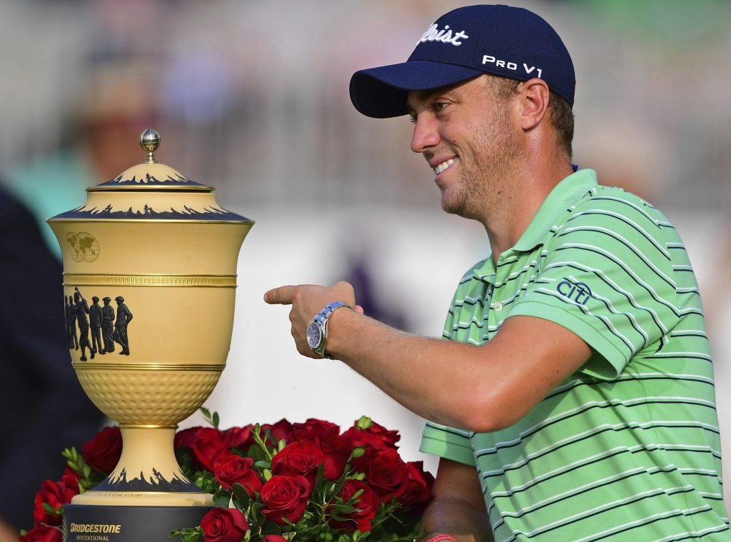 Justin Thomas points the Gary Player Cup trophy after winning the Bridgestone Invitational on Sunday at Firestone Country Club in Akron, Ohio.
