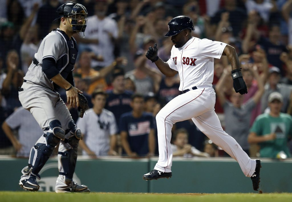 Boston's Jackie Bradley Jr., right, scores in front of New York's Austin Romine after a throwing error by Miguel Andujar to tie the game at 4-4 in the ninth inning Sunday at Fenway Park in Boston. The Red Sox won in the bottom of the 10th, 5-4.