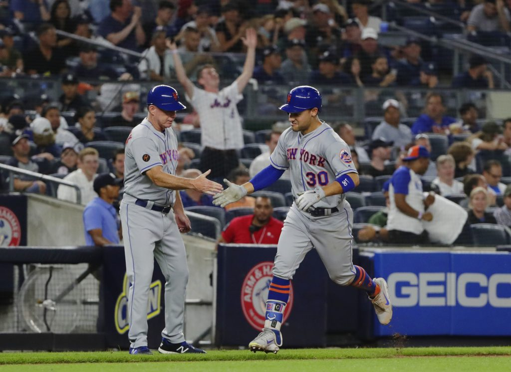 New York Mets' Michael Conforto, right, celebrates with third base coach Glenn Sherlock after hitting one of the Mets five home runs in their win over the Yankees on Monday in New York.