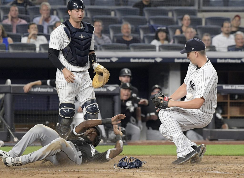 Chicago White Sox runner Tim Anderson, bottom left, scores on a wild pitch as New York Yankees pitcher A.J. Cole, right, cannot handle the throw from catcher Kyle Higashioka, top left, during the ninth inning on Monday at Yankee Stadium in New York.