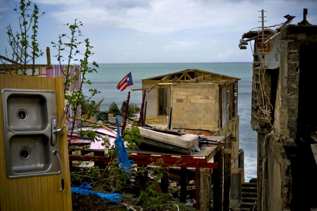 A Puerto Rican national flag is mounted on a damaged home in the seaside slum of La Perla, San Juan, in the aftermath of Hurricane Maria on Oct. 5. An independent investigation ordered by Puerto Rico's government estimates that nearly 3,000 people died as a result of Hurricane Maria. The findings by the Milken Institute School of Public Health at George Washington University contrast sharply with the official death toll of 64.