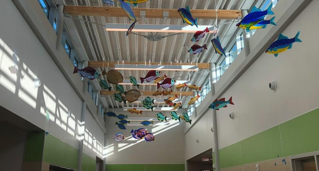 Artist Janet Redfield created the glass fish installation that hangs in the entryway of the new school.