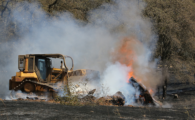 A Cal Fire bulldozer pushes through a mound of burning vegetation in Grass Valley, Calif. on Wednesday.