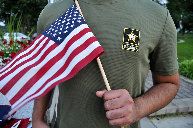 A Pakistani recruit, 22, who was recently discharged from the U.S. Army, holds an American flag as he poses for a picture.