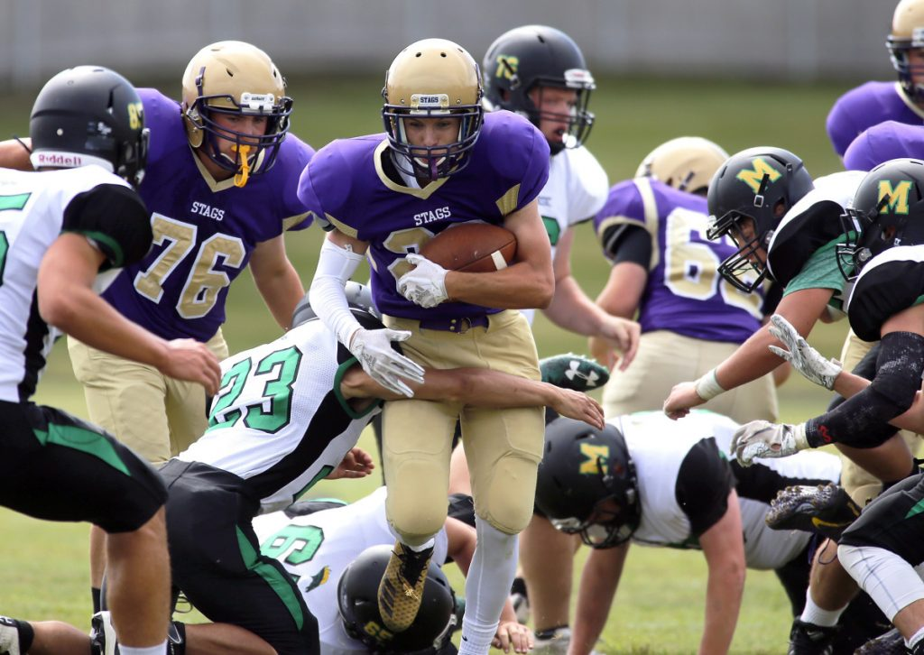 Nick Hutton of Cheverus tries to break a tackle by Massabesic's Ben Rohner during a Class A football game Saturday at Boulos Stadium. Cheverus won, 43-6.