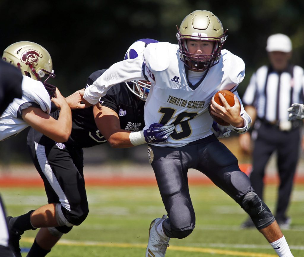 Thornton Academy quarterback Kobe Gaudette tries to shed a defender Saturday against Deering at Fitzpatrick Stadium. The Golden Trojans started their season with a 70-0 victory.