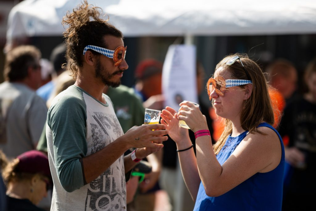 Chance Gonyer of Cornville and Leah Agren of Norridgewock share sips of brew samples at the Skowhegan Craft Brew Festival on Saturday. A few were walking around the festival Saturday afternoon while wearing pretzel glasses.