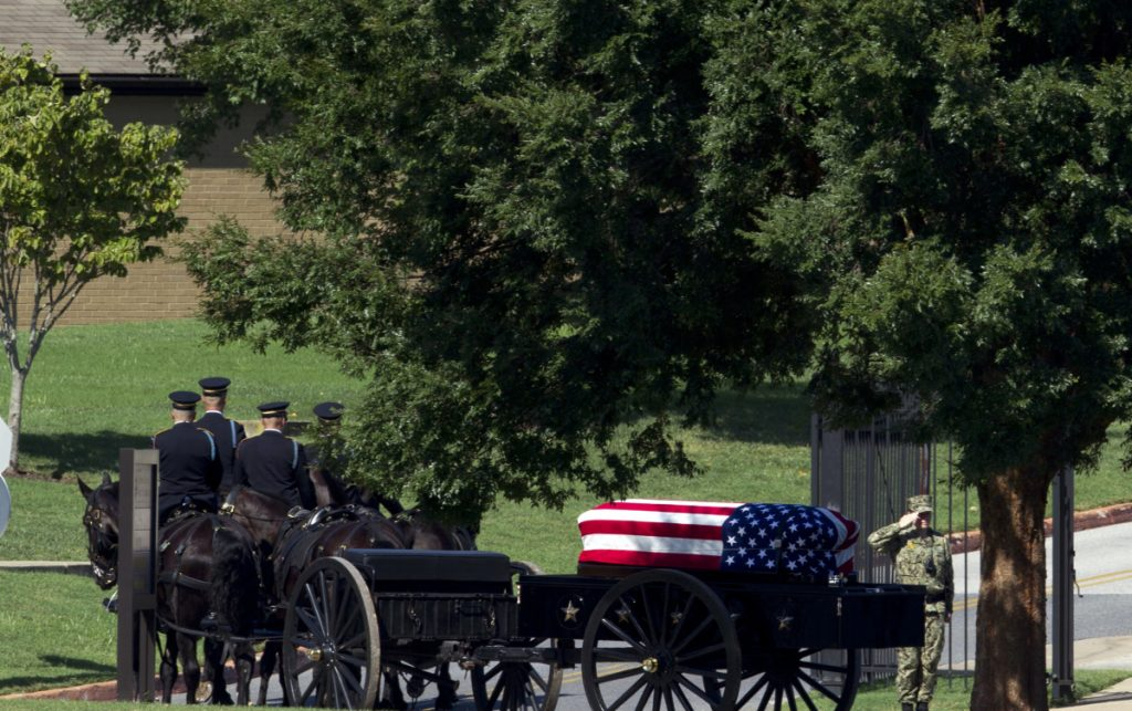 A horse-drawn caisson carries the casket containing Sen. John McCain, R-Ariz., to his burial site at the U.S. Naval Academy Cemetery in Annapolis, Md., on Sunday. McCain died Aug. 25 from brain cancer at age 81.