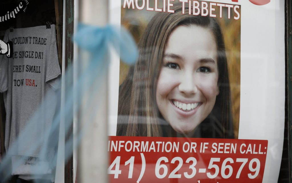 A poster for University of Iowa student Mollie Tibbetts hangs in the window of a business in Brooklyn, Iowa.
