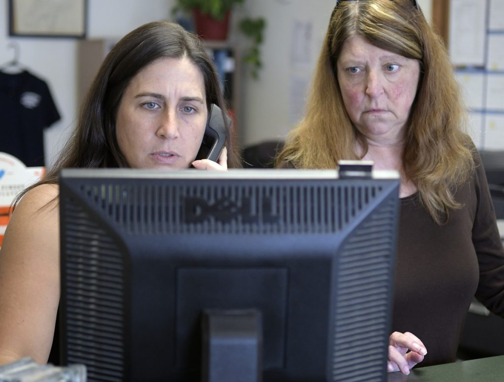 Deputy Clerk Lezley Sturtevant and Town Manager Trudy Lamoreau help a Litchfield resident at the town office. The town lost about a month's worth of backup data when its computers crashed in July.